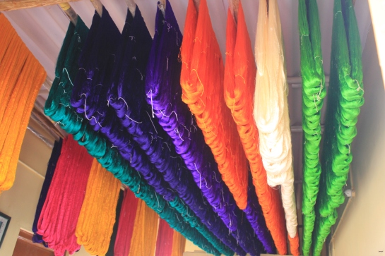 Silk yarn dyed in various hues being left to dry.