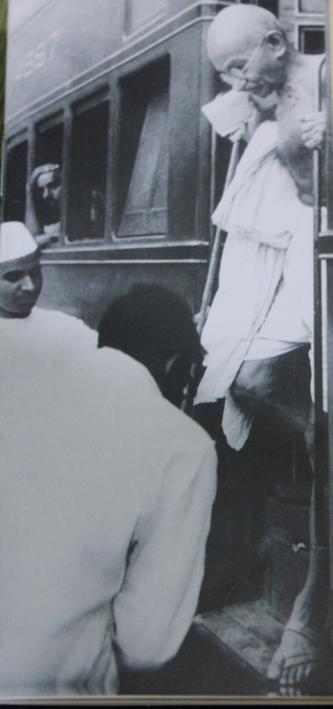 Gandhi alighting from a third-class train carriage.